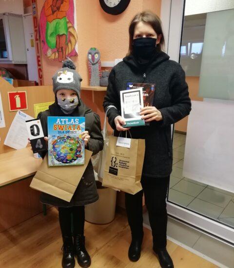 kobieta w czarnej kurtce z zasłoniętymi ustami i nosem, w rękach trzyma czytnik ebooków oraz torbę papierową. Z lewej strony zdjęcia stoi dziewczynka w kolorowej czapce, w rękach trzyma ksiązkę i smartbanda w opakowaniu.
