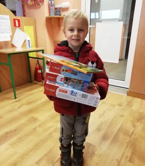 mały chłopiec o jasnych włosach, ubrany w bordową kurtkę. W rękach trzyma gry planszowe, na których położona jest książka.