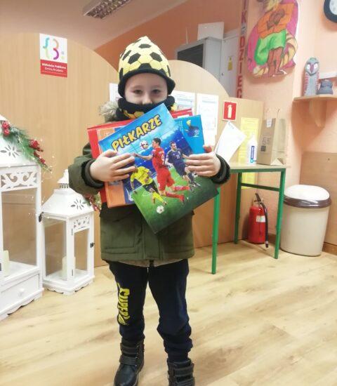 mały chłopiec ubrany w ciemnozieloną kurtkę i żółto-czarną czapkę. W rękach trzyma grę planszową i książki.