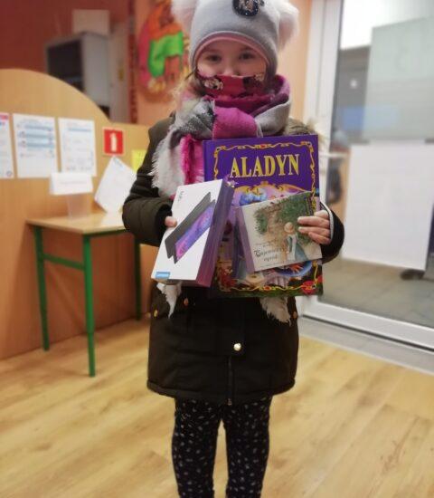 dziewczynka trzyma w rękach tablet i ksiązkę. Na głowie ma jasnoszarą czapkę, nos i usta ma zasłonięte kolorową chustą