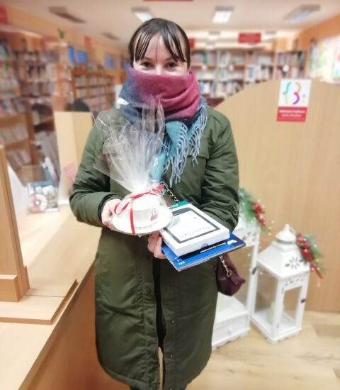 na zdjęciu kobieta z kolorową chustą zasłaniającą nos i usta. W rękach trzyma filiżankę owiniętą w folię oraz książkę i czytnik ebooków. W tle jasne meble biblioteczne.