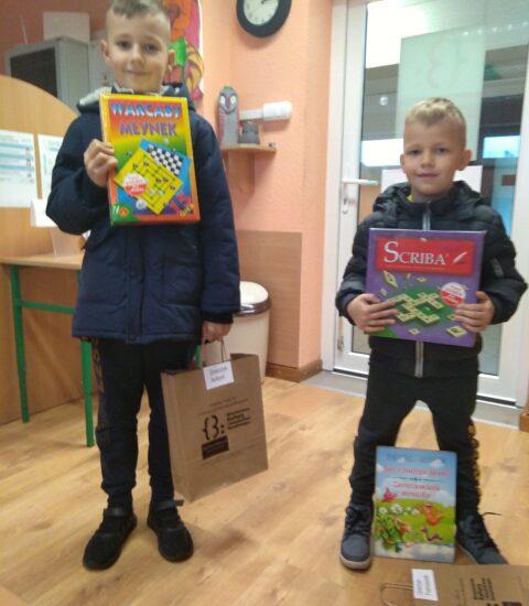 dwóch uśmiechniętych chłopców w ciemnych kurtkach. Wyższy stoi po lewej strone. obaj trzymają nagrody w postaci gier planszowych.
