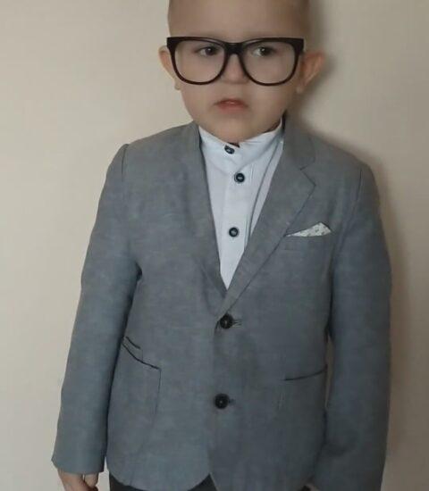 chłopiec w okularach, ubrany w szarą marynarkę i białą koszulę