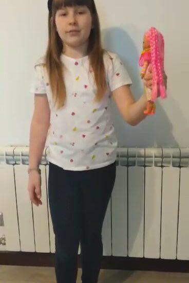 dziewczynka trzyma ręku małą lalkę
