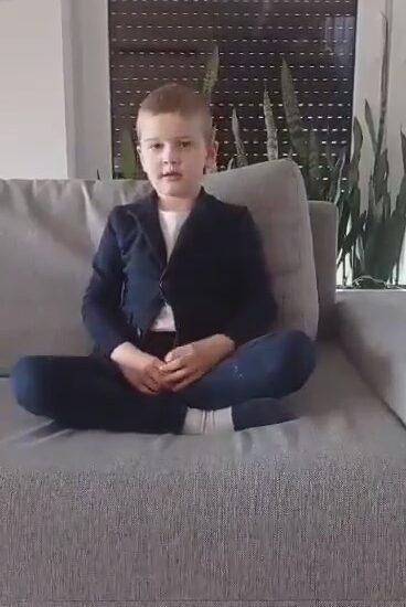chłopiec ubrany w szarą marynarkę i ciemne spodnie, siedzi na kanapie