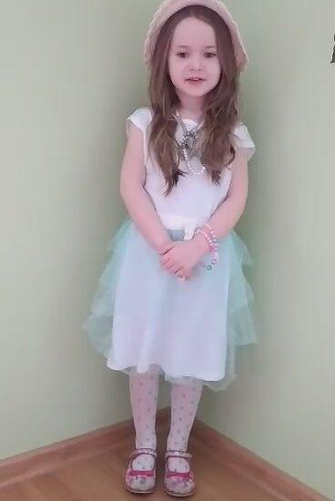dziewczynka ubrana w białą bluzkę, jasną spódnicę, na głowie różowy kapelusz
