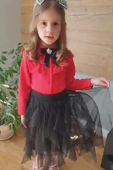 dziewczynka ubrana w czerwoną bluzkę i czarną spódnicę, na głowie opaska