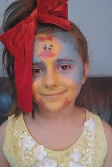 dziewczynka z pomalowaną twarzą, na głowie duża czerwona kokarda