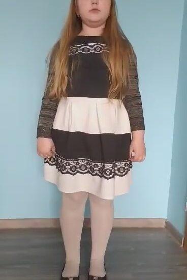 dziewczynka w sukience, stoi na tle błękitnej ściany