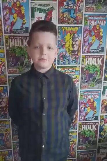 chłopiec ubrany w ciemną koszulę, w tle kolorowe plakaty