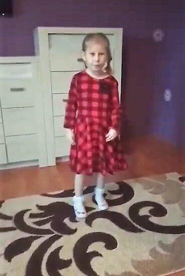 dziewczynka ubrana w sukienkę, stoi na dywanie, w tle białe meble