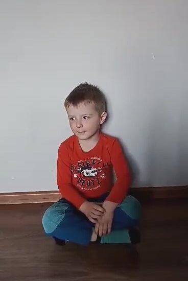 chłopiec siedzi na podłodze, ubrany w czerwoną bluzkę
