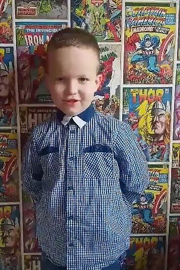 chłopiec ubrany w koszulę, w tle kolorowe plakaty