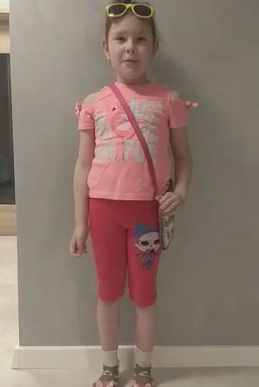 dziewczynka ubrana w różową bluzkę i czerwone spodenki, przewieszona czerwona torebka