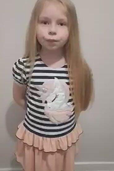 dziewczynka w jasnych, długich włosach, ubrana w bluzkę w paski i jasną spódnicę