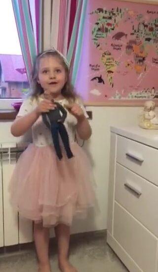 dziewczynka ubrana w białą bluzkę i różową spódnicę, w ręku trzyma lalkę