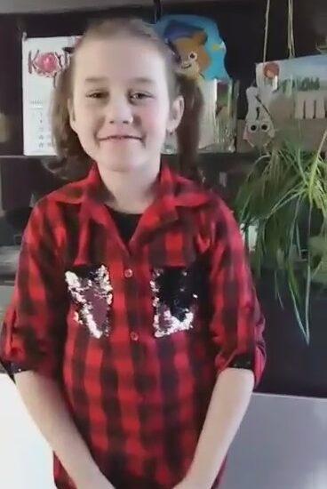 dziewczynka ubrana w koszulę w kratę, w tle ciemne meble