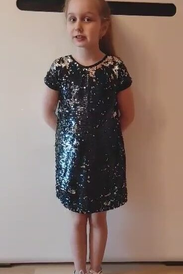 dziewczynka ubrana w ciemną, błyszczącą sukienkę
