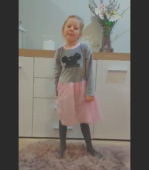 dziewczynka w sukience stoi na dywanie, w tle jasne meble