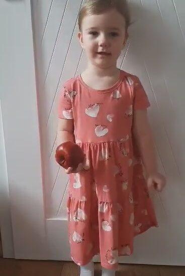 dziewczyna ubrana w sukienkę, w ręku trzyma jabłko