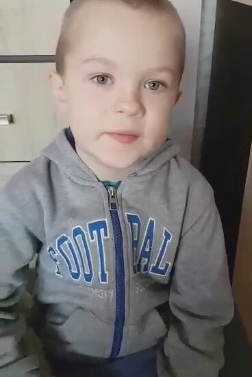 chłopiec ubrany w szarą bluzę