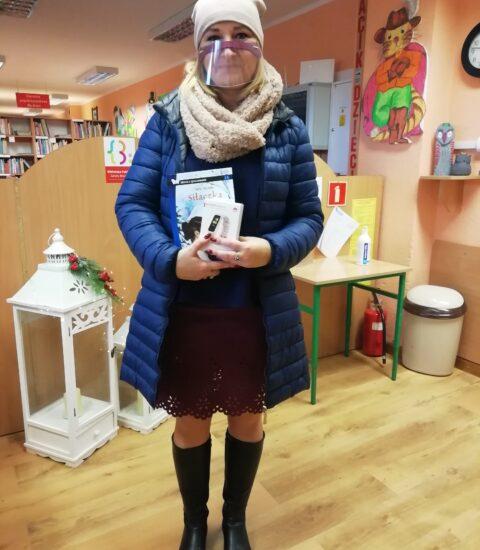 kobieta w jasnej czapce na głowie, ubrana w ciemnoniebieską kurtkę. W rękach trzyma ksiązkę i smartbanda w opakowaniu. na twarzy ma przezroczystą maseczkę.