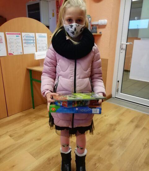 dziewczynka o jasnych włosach, ubrana w różową kurtkę i czarny komin, trzyma w rękach książkę i grę planszową.