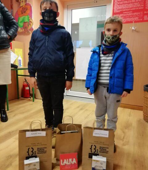 dwóch chłopców. Wyższy ubrany jest w granatową kurtkęi ciemny komin na twarzy. Niższy ma rozpiętą niebieską kurtkę. Przed nim na podłodze stoją trzy torby papierowe oraz płyty, słuchawki w opakowaniach.