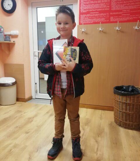 uśmiechnięty chłopiec. W rękach trzyma tablet i plytę. Ubrany w ciemną bluzę z czerwonym kapturem.