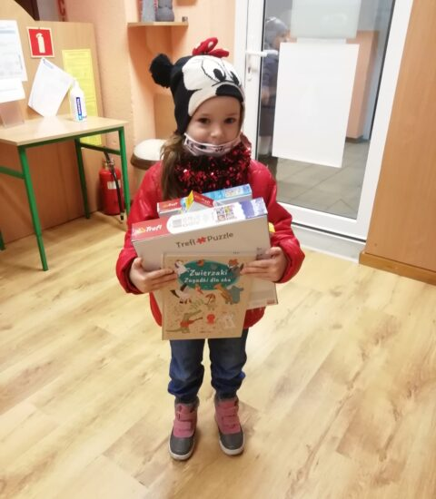 mała dziewczynka, trzyma w rękach gry planszowe, ubrana w czerwoną kurtę. Na głowie ma kolorową czapkę.