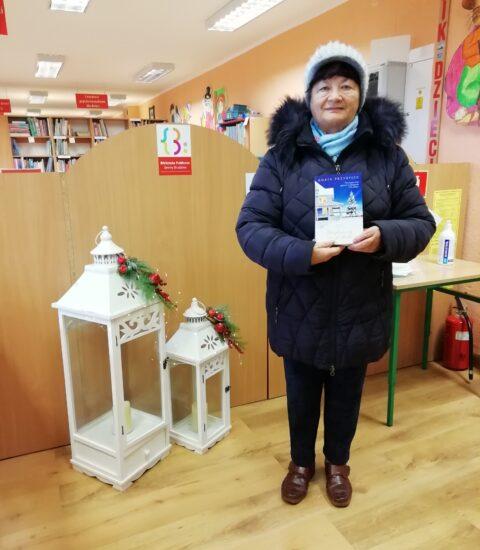 kobieta w granatowej kurtce, jasnej czapce trzyma w rękach ksiązkę. W tle jasne meble biblioteczne i dwa białe lampiony
