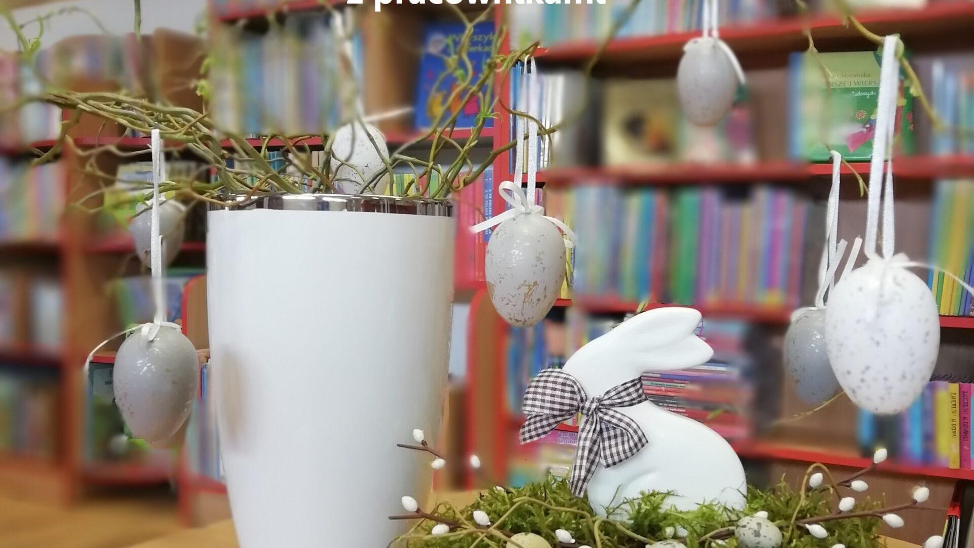 na stoliku biały wazon z wiszącymi jajkami w kolorze białym i szarym, obok stroik wielkanocny, w tle regały z książkami