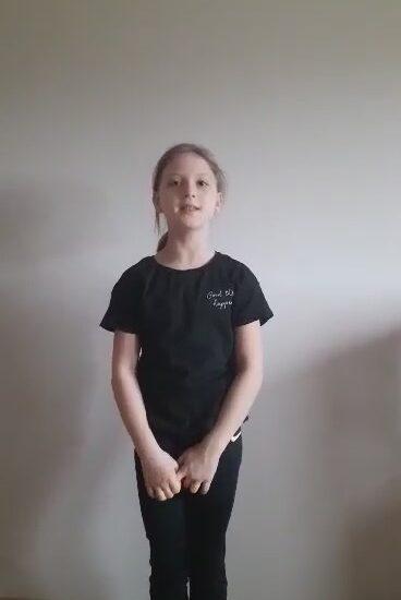 dziewczynka ubrana na czarno, stoi na tle jasnej ściany