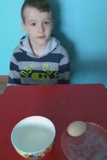 chłopiec siedzący przy stole, na stole miska z mlekiem i jajko