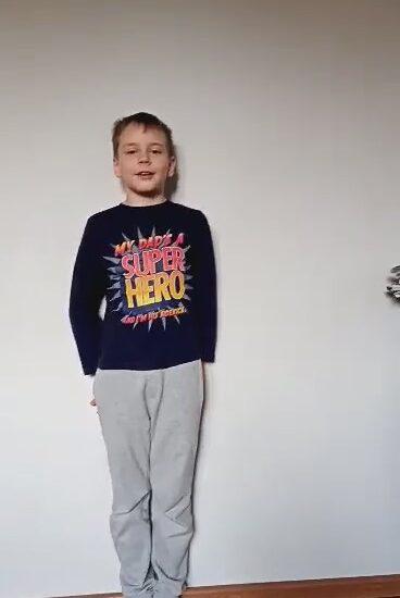 chłopiec ubrany w jasne spodnie i ciemną bluzkę, stoi na tle jasnej ściany