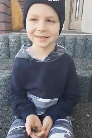 chłopiec ubrany w czapkę i bluzę, siedzi na schodach