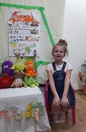 dziewczynka siedzi przy stoliku, na którym znajdują się pluszowe warzywa