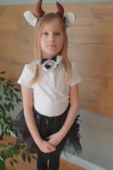 dziewczynka ubrana w białą bluzkę i czarną spódnicę, na głowie opaska w postaci rogów