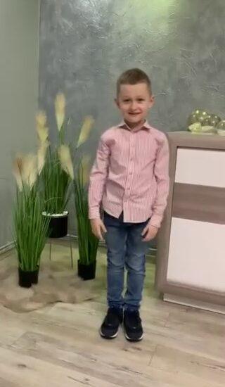 chłopiec ubrany w różową koszulę i jeansy, w tle trzy doniczki z kwiatami