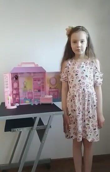 dziewczynka ubrana w kolorową sukienkę, na stoliku obok różowy dom dla lalek
