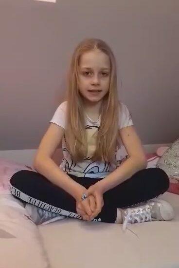 dziewczynka w rozpuszczonych jasnych włosach siedzi na łóżku