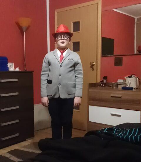 chłopiec w jasnej marynarce, w kapeluszu na głowie stoi w pokoju, w tle widać ciemne meble