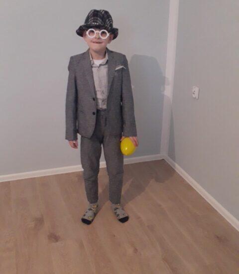 chłopiec ubrany w szarą marynarkę i spodnie, na głowie kapelusz i okulary, w ręku trzyma plastikowe jajo