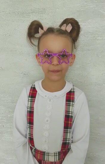 dziewczynka w różowych okularach na twarzy, ubrana w białą bluzkę