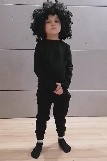 chłopiec ubrany na czarno, na głowie duża, czarna peruka