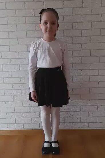 dziewczynka ubrana w białą bluzkę i czarną spódnicę, na głowie opaska