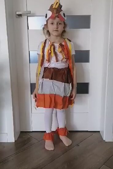 dziewczynka przebrana za kurę, w tle białe drzwi