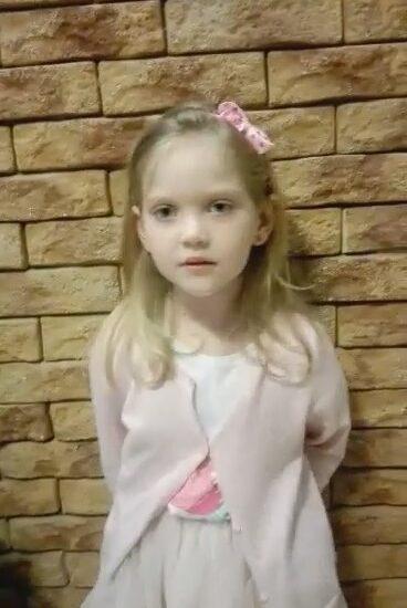 dziewczynka ubrana w różowy sweterek, na głowie różowa opaska