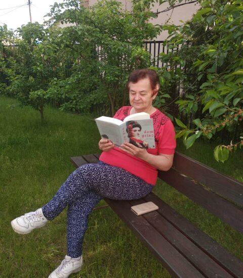 kobieta z książką w rękach siedzi na ławce