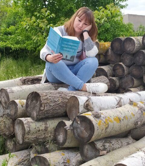 kobieta z otwartą książką w rękach siedzi na ściętych pniach drzewa